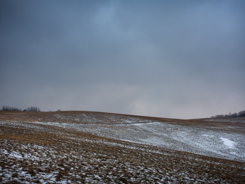 Photographic image of Washington county, NY with rolling hills crusted with snow and a dramatic sky.