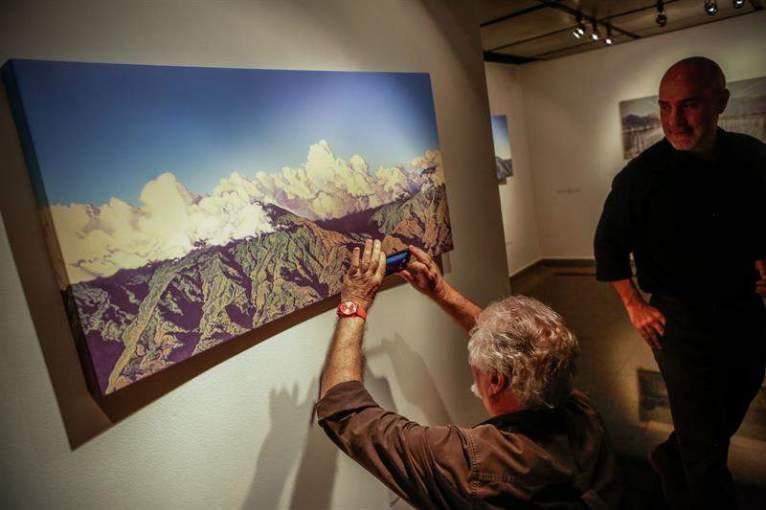 """Fotografía del 10 de octubre de 2017, que muestra a personas mientras observan la obra """"Cordillera, atardecer con nubes desde Cerro Verde"""", de Roberto De La Fuente, que hace parte de la exposición """"Caracas, un lugar"""" Foto EFE"""