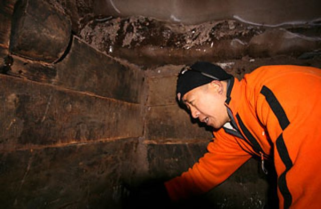 An explorer looks at wooden beams inside a compartment of a structure that his team claims might prove the existence of Noah's Ark, on Mount Ararat