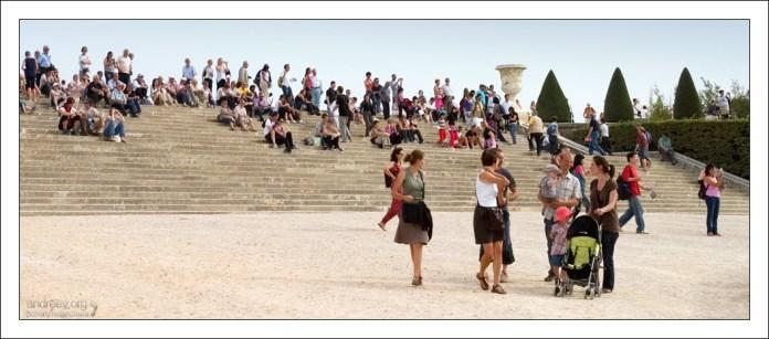 Туристы отдыхают в Версальском парке.