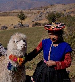 Местная женщина в традиционном платье с годовалой альпакой.
