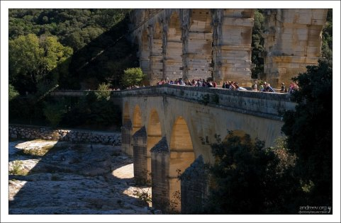 Туристы курсируют по нижнему ярусу моста Пон-дю-Гар с берега на берег.