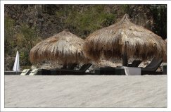 Лежаки и зонтики из тростника на черном вулканическом пляже Ансе Частанет.