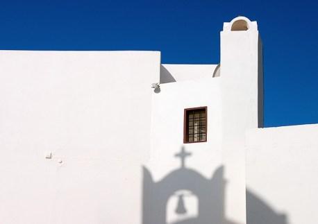 Тень от колокола на белоснежной стене одного из домов в Ие.