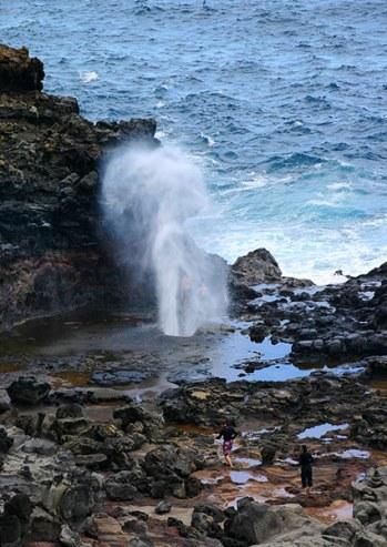 Люди, пробирающиеся через лаву к фонтану Nakalele blowhole.