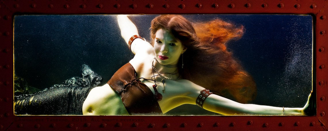 A white mermaid with long red hair floating behind her and brown leather, steampunk costume.