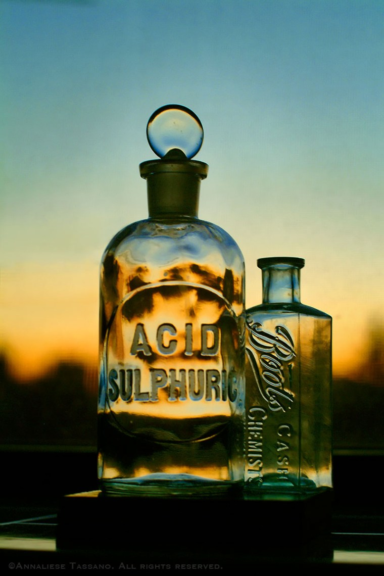 Antique glass bottles, on with a glass stopper, reading Acid Sulphuric and Boots Chemists cash, sit in a window as the sunset fades outside, in Brooklyn, New York.