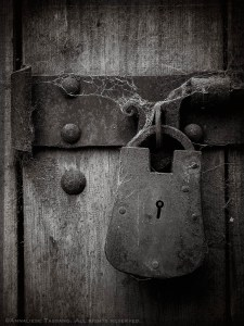 Covered in cobwebs, a sturdy, rustic lock does the job of securing a storeroom's heavy, rough wooden door.