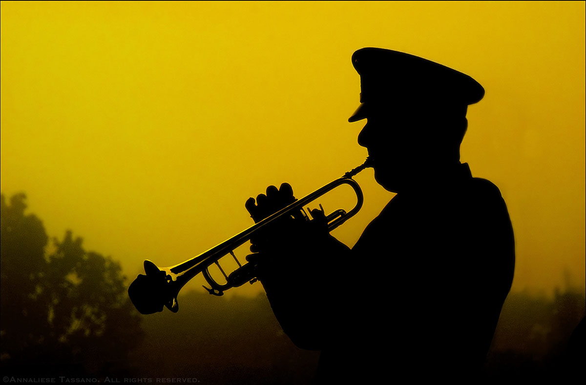 The silhouette of a military trumpeter playing taps in front of a yellow dawn sky at a September 11, 2002 memorial.