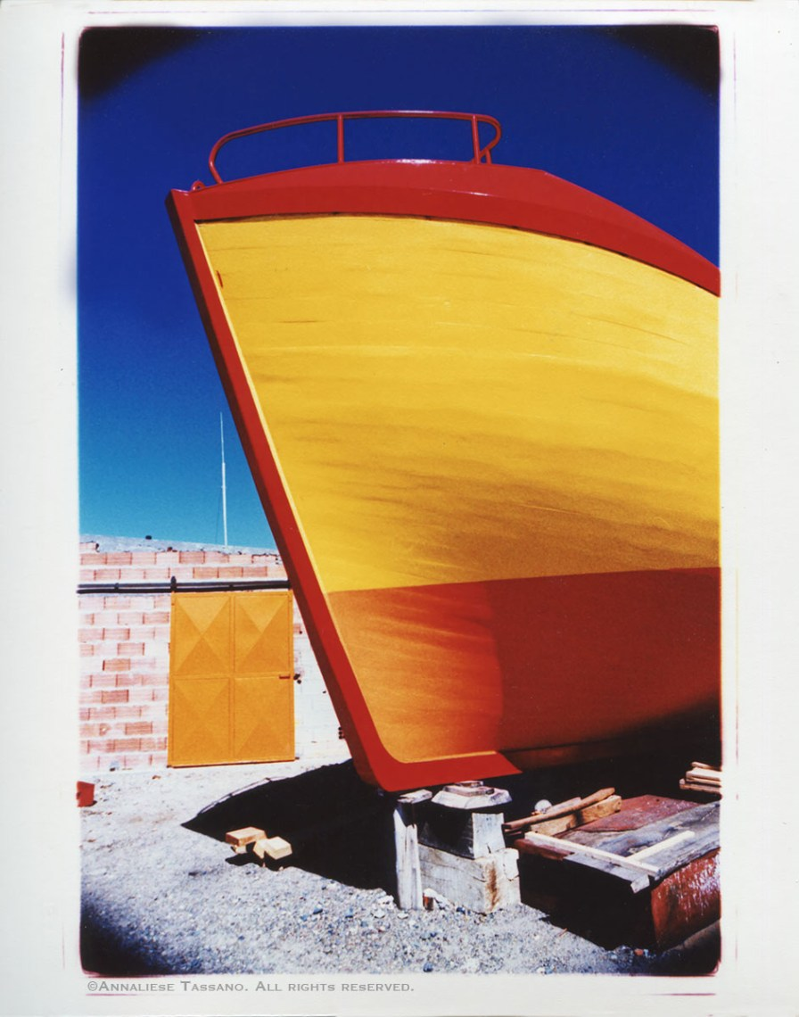 A cross process photo shows a finished wooden fishing boat painted bright yellow, orange, and red. A brick wall with al large orange door and a a ricj blue sky in the background.