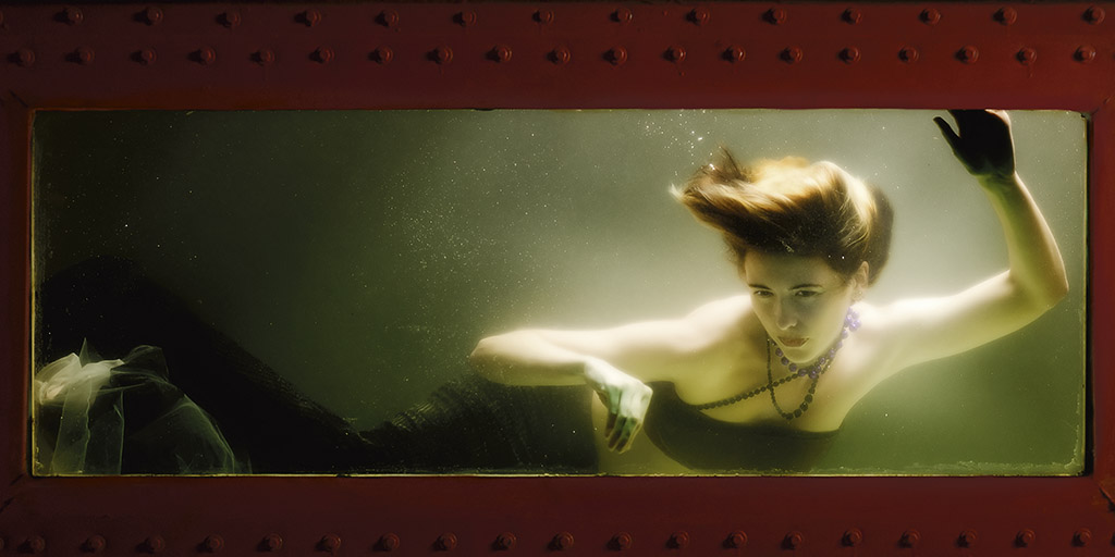 A fair skinned mermaid with short brown hair is confined in a tank.