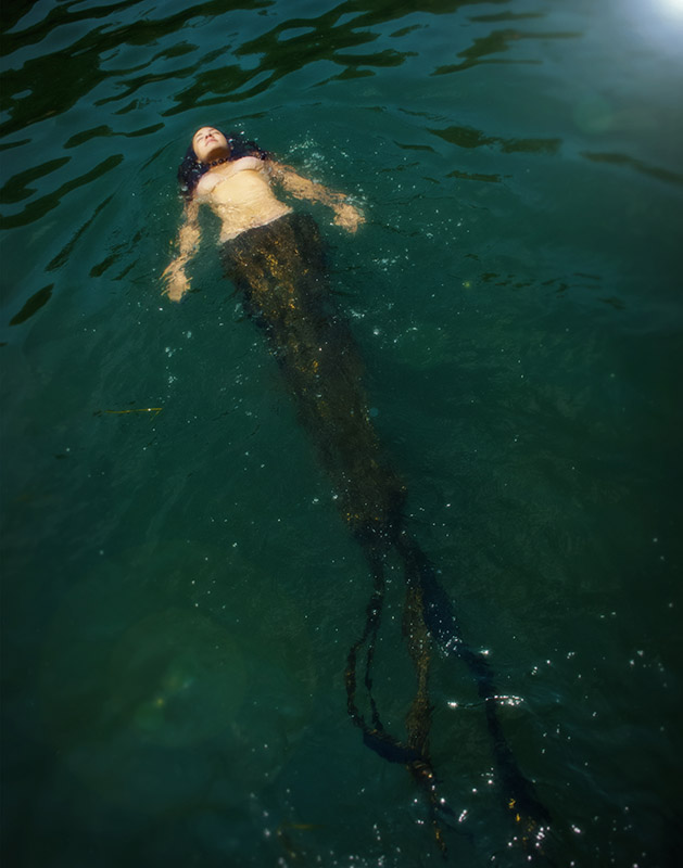 A beautiful young mermaid floats in green waters, sparkling in the sunlight.