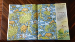 Endpapers of book show dragons wheeling through air.