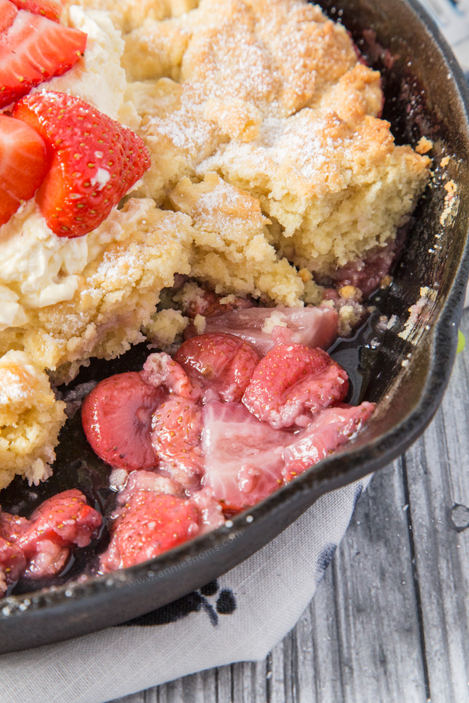 This Strawberry Shortcake Cobbler is filled with juicy strawberries, topped with a light as air shortcake and whipped cream; the perfect Summer dessert for sharing!