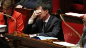 French Prime Minister Manuel Valls (C) reacts during a session of questions to the government at the French National Assembly in Paris on December 9, 2015.  / AFP PHOTO / PATRICK KOVARIK