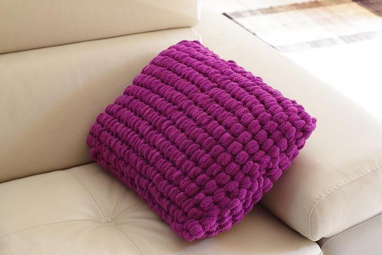 Tricot : un coussin de canapé en laine pompon - APODIOXE