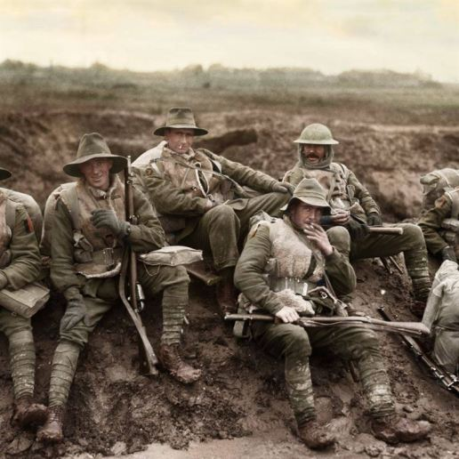 Unidentified men of the Australian 5th Division enjoying a smoke and rest by the side of the Montauban road, near Mametz, France, while en-route to the trenches. Most of the men are wearing sheepskin vests and woollen gloves, and are carrying full kit and .303 Lee Enfield rifles, December 1916.
