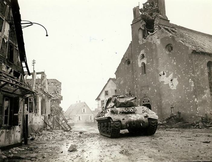 M-10 Tank Destroyer passing through an unknown German Town in 1945, you can see the town's church damaged by shell blasts.