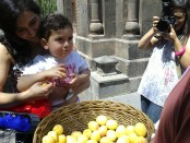 A child samples the blessed apricots. (Photo by Harout Ekmanian)