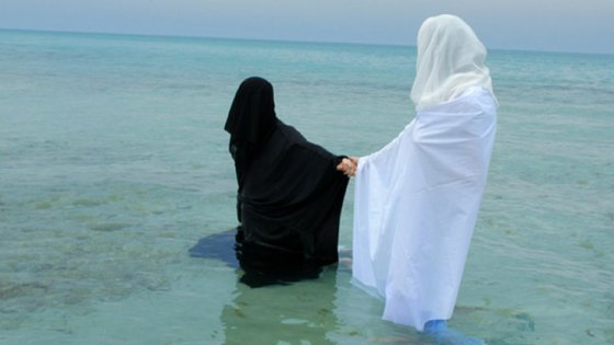 woman in black robe holding hand of woman in white robe in body of water