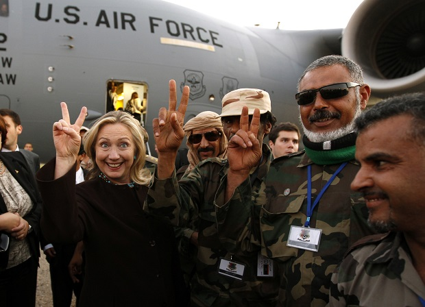 U.S. Secretary of State Hillary Clinton (C) gestures with Libyan soldiers upon her departure from Tripoli in Libya October 18, 2011.  REUTERS/Kevin Lamarque  (LIBYA - Tags: POLITICS TPX IMAGES OF THE DAY MILITARY) - RTR2ST1X