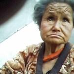 """노상에 주저앉아 식품을 파는 노파. 잘 팔리지 않는 모양인지 활기가 없었다. 2013년 6월 양강도 혜산시에서 촬영 """"민들레""""(아시아프레스)"""