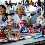평양 중심부에 위치한 모란 시장의 식품 매장. 가격표는 조선원이지만, 미국 달러나 위안화, 유로, 일본엔이 환영 받는다. 일하는 여성들은 점원이 아니라 폭 80센티의 매장 경영자다. 2011년 7월 촬영 구광호(아시아프레스)