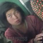 중학생으로 보이는 소녀가 시장 안에서 연탄불을 쬐고 있다. 2012년 11월 양강도 혜산시에서 촬영 아시아프레스