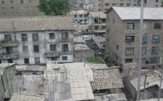 오른쪽에 보이는 아파트는 블록이 노출된 채로 외벽 공사가 미완성이지만, 입주하고 있다. 2008년 6월 평안남도에서 촬영 백향(아시아프레스)