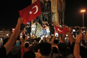 Supporters of Turkey's President Recep Tayyip Erdogan, gather, waving Turkish flags, in Istanbul's Taksim square, early Saturday, July 16, 2016.  Members of Turkey's armed forces said they had taken control of the country Friday as explosions, gunfire and a reported air battle between loyalist forces and coup supporters erupted in the capital. President Erdogan remained defiant and called on people to take to the streets to show support for his embattled government.(AP Photo/Emrah Gurel)