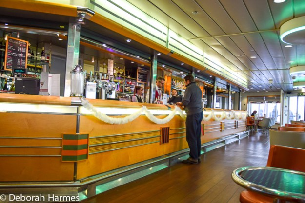 During an afternoon crossing between England and France, Mark is buying 2 expressos at the bar on one of the upper decks of the Brittany Ferry.