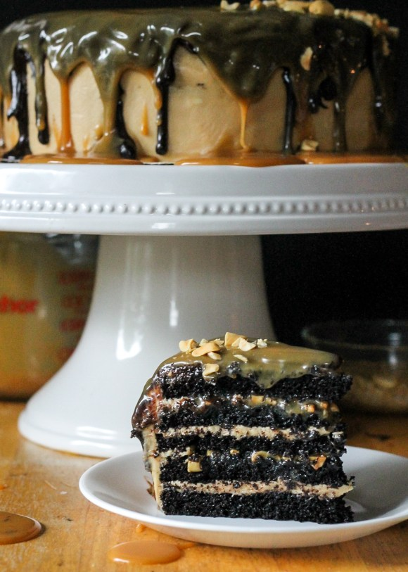The Ultimate Snickers Cake | Dark chocolate cake, peanut caramel filling, peanut butter cream cheese frosting, with chocolate ganache and caramel. Recipe from Bakerita.com