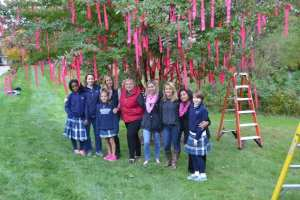 """Members of the Garrison Forest School community stand in front of the """"Tree of Hope""""."""