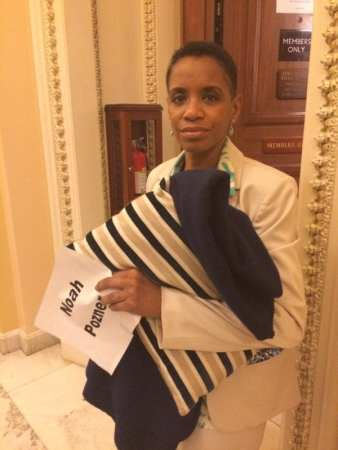 Rep. Donna Edwards with a sign bearing the name of a victim of gun violence, and a blanket for her sleepover on the House floor. Photo via @isabelalbee