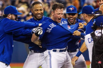 Toronto Blue Jays Josh Donaldson is mobbed by his teammates as he celebrates hitting the winning home run in the 10th inning against the Atlanta Braves during MLB action in Toronto Saturday, April 18, 2015. THE CANADIAN PRESS/Aaron Vincent Elkaim