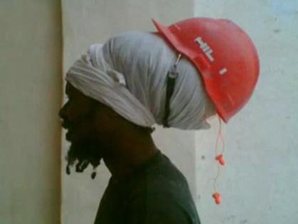 Bauarbeiter trägt Sicherheitshelm auf Haaren
