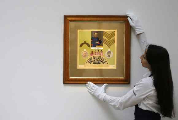 Sotheby's employee adjusts Sgt Pepper collage by Peter Blake and Jann Haworth