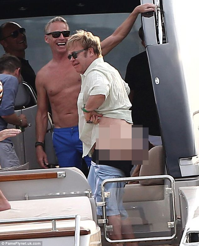 Sir Elton John flashes a passing yacht while enjoying his stay in St Tropez