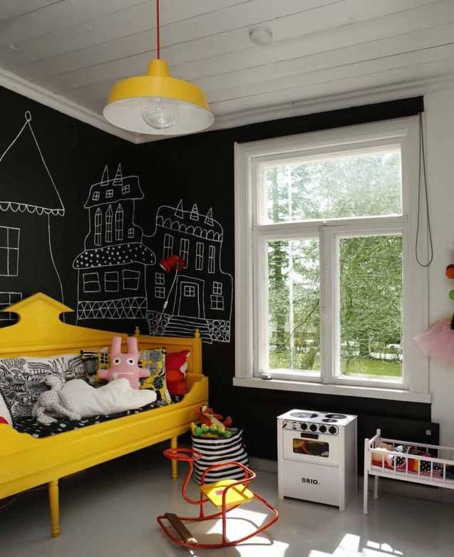 Bunte Kindermöbel vor schwarzer Wand mit Tafelfarbe