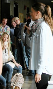 Female livestock judging student evaluating pumpkins