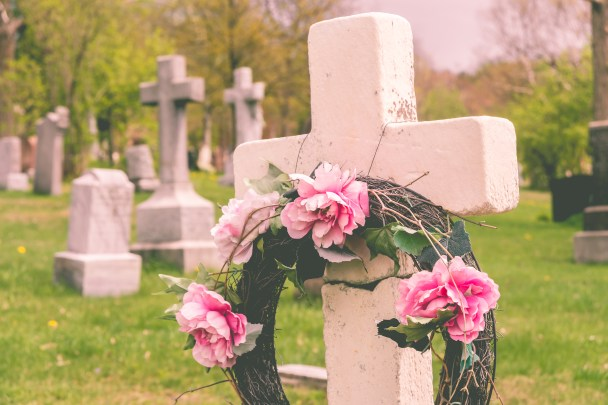 Funeral wreath with pink flower on a cross in a cemetary with a vintage filter.