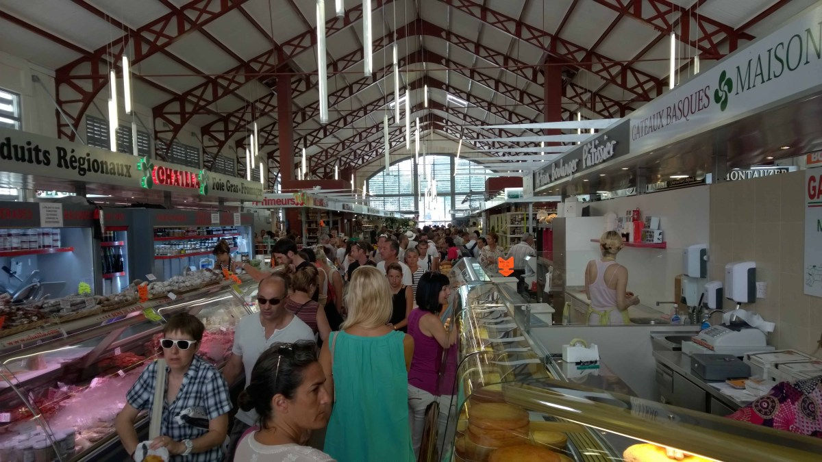 Photograph of interior of Biarritz market with stalls and lots of people.