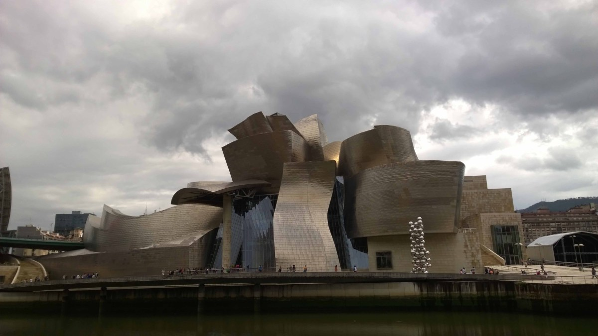 Photograph of the Guggenheim, Bilbao from the other side of the river which runs next to it.