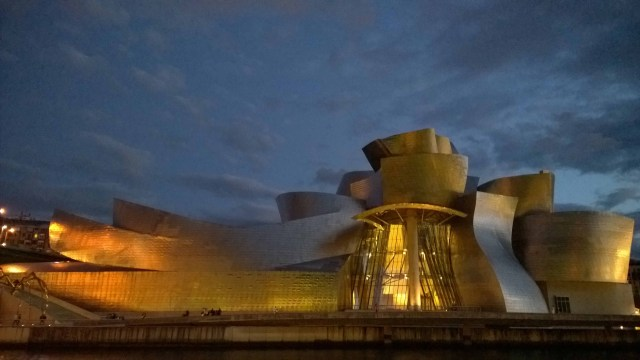 Photograph of the Guggenheim Art Gallery, Bilbao lit up at night.