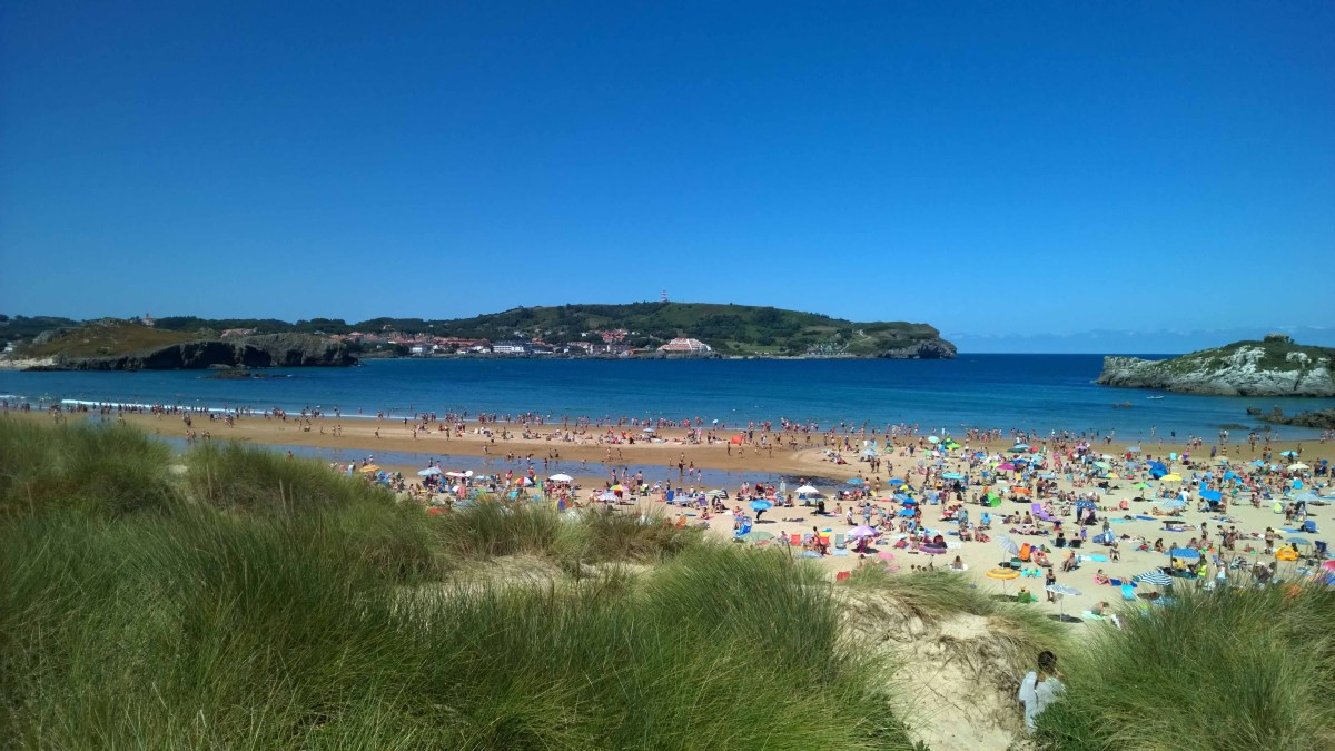 Photograph of a crowded beach and blue sea beyond at Noja, Spain.