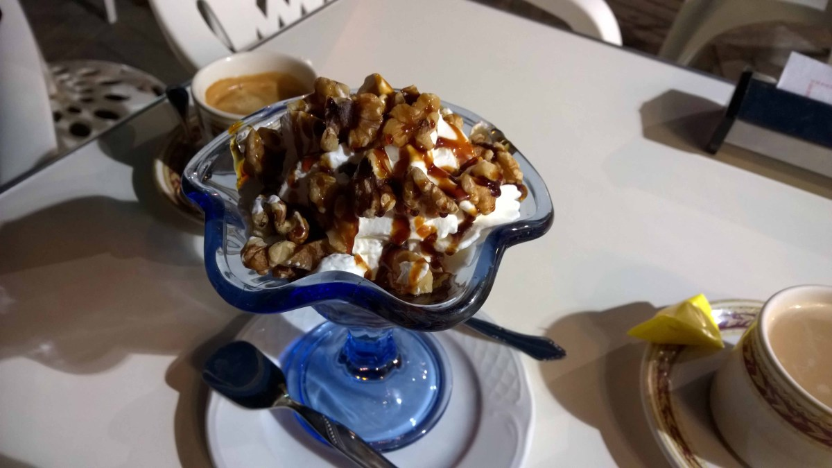 Photograph of a blue ice cream dish full of whipped cream and walnuts and covered in sauce.