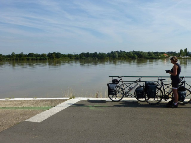 Photograph of Sarah standing on River Loire quayside next to two bicycles.