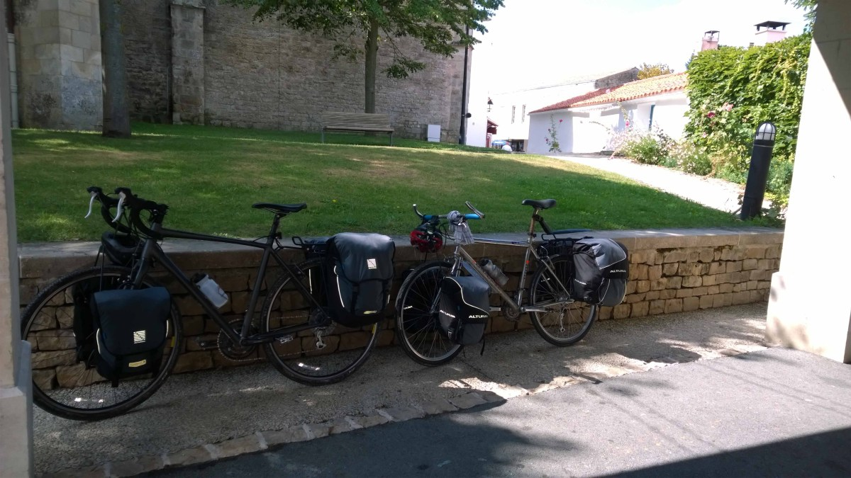 Photograph of two bicycles leaning up against a churchyard wall with a church in the background.