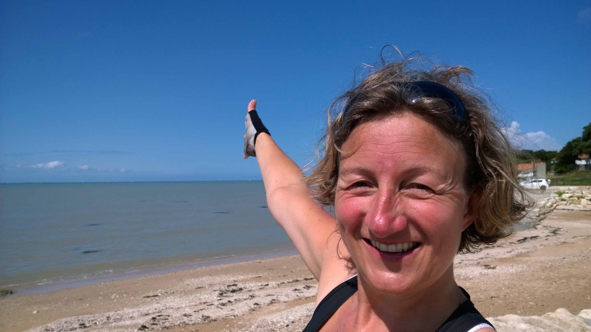 Photograph of Sarah pointing at the sea behind her.