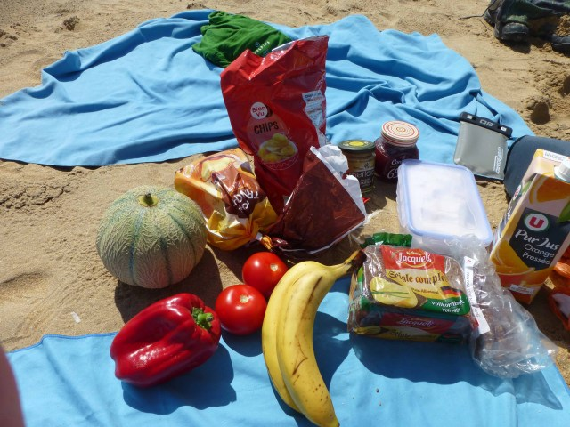 Photograph of various picnic food items spread out on a beach in France.